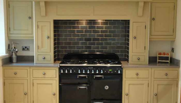 Aga cooker in timber surround with brickwork tiled upstand to rear