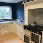 Kitchen floor cupboards, range style cooker in housing and sink with view out of window